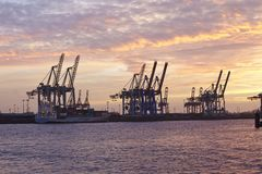Hamburg - Hafen bei Sonnenuntergang mit BehälterPortalkränen stockfotografie
