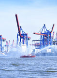 Hamburg harbor cranes and firefighter ship with water fountains Stock Photography
