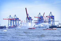 Hamburg harbor cranes and firefighter ship with water fountains Royalty Free Stock Image