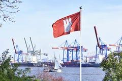 Hamburg harbor cranes and Hamburg flag in focus Royalty Free Stock Image