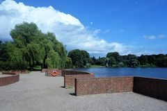 Hamburg Park. Clouds over the trees and water in a park in Hamburg Germany stock image