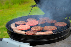 Hamburg patties and bratwurst grilling Royalty Free Stock Image