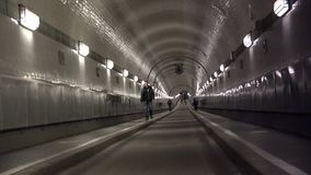 HAMBURG  People walk through the old Elbe tunnel in Hamburg Germany. Event with more than 1.5 million visitors & 300 guest ships stock video footage