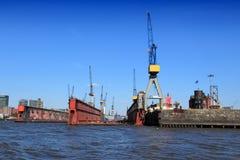 Hamburg port. Hamburg, Germany - famous port seen from river Elbe. Industrial harbor cranes Royalty Free Stock Photos