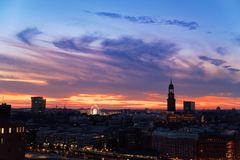 Hamburg at sunset scene with Dancing Towers, Ferris Wheel of Hamburg`s Dom and St. Michaelis church in a distant. Hamburg`s landmarks at sunset - Dancing towers stock photography