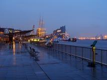 Hamburg Tyskland - April 04, 2016: Öde port av Hamburg på en regnig dag i aftonen med upplysta Elbphilharmonie royaltyfri fotografi