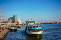 HAMBURG TYSKLAND - April 18, 2018: Landningställe för St Pauli Landungsbrucken i port av Hamburg mellan den lägre hamnen royaltyfri fotografi