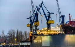 Hamburg Tyskland, December 10th 2017: Behållarekranar på skeppsdocka 1 Arkivfoton