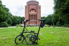 Hamburg Tyskland - Juli 14, 2018: Cykeln för upplaga för Brompton svartfärg framme av planetariet royaltyfri foto