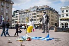 Hamburg Tyskland - Juni 23, 2014: Gatakonstnärer utför visuell konst för svävning nära Rathausmarkt, medan folket går den förvåna Arkivbilder