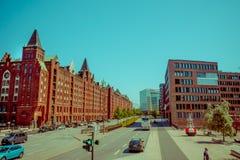 HAMBURG TYSKLAND - JUNI 08, 2015: Historiska byggnader all gata länge i Hamburg, bilar och bussar som passerar trought Arkivbild