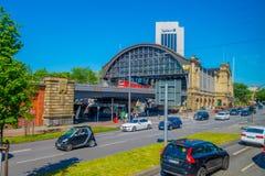 HAMBURG TYSKLAND - JUNI 08, 2015: Sikt för Dammtor drevstation från gatan, kommande rött drev ut Royaltyfri Bild