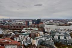 HAMBURG TYSKLAND - MARS 27, 2016: Scenisk panorama över Landungsbruecken, nya Elbphilharmonie, floden Elbe och skeppsdockor in Arkivbilder
