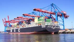 HAMBURG TYSKLAND - MARS 8th, 2014: Sikt på Burchardkaien av den Hamburg hamnen Behållareskeppet från MSC är olastat Arkivfoton