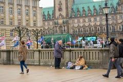 Hamburg Tyskland, 22 November 2017 Medborgaren meddelar med en hemlös person som framme sitter på jordningen av den hal staden royaltyfri foto