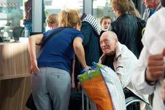 HAMBURG TYSKLAND - SEPTEMBER 03, 2017: En flicka transporterar en äldre man i en rullstol arkivfoto