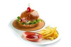Hamburgare, franska sm?fiskar och tomats?s i en vit oval platta som isoleras p? vit bakgrund arkivfoto