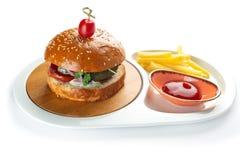 Hamburgare, franska sm?fiskar och tomats?s i en vit oval platta som isoleras p? vit bakgrund royaltyfria bilder