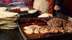 Hamburgare kött, bröd, korvar stekas på ett galler, män som ` s räcker att vända dem stock video