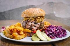 Hamburgare med bacon, grönsaker och potatisar Royaltyfri Foto