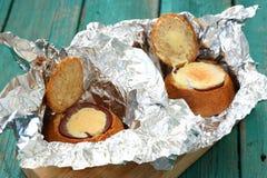Hamburgare med bakad ägg och skinka i folie Royaltyfri Bild