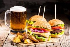 Hamburgare med nötkött och stekt potatisar och exponeringsglas av kallt öl arkivfoton