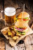 Hamburgare med nötkött och stekt potatisar och exponeringsglas av kallt öl arkivbilder