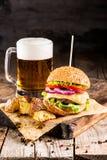 Hamburgare med nötkött och stekt potatisar och exponeringsglas av kallt öl arkivfoto
