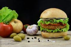 Hamburgare med nya grönsaker på träskrivbordet Royaltyfri Fotografi