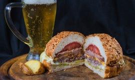 Hamburgare med potatisen och öl royaltyfri fotografi