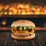 Hamburgare med stekt patato och ost på trätabletopen med den suddiga stången på bakgrunden Fastfood som annonserar begrepp royaltyfria foton