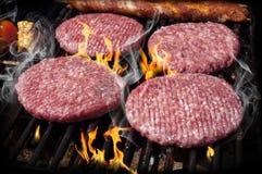 Hamburgare, nötkött och korvar på ett galler med flammor arkivbild