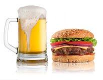 Hamburgare och exponeringsglas av öl som isoleras på vit Arkivfoto