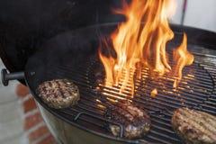 Hamburgare på en varm grillfest med brand arkivfoto