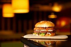 Hamburgare som tjänas som på träplankor Hemlagad hamburgare med grönsallat och ost Royaltyfria Foton