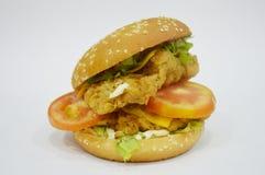 Hamburgare - stor saftig hamburgare på vit bakgrund - brännboll Arkivbild