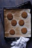 Hamburgareingredienser, hemlagade små pastejer på bakplåten över träbakgrund Royaltyfri Bild
