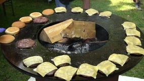 Hamburgarekött-, ost- och brödbakning på utomhus- galler Ultrarapidskott lager videofilmer
