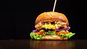 Hamburgaren lagar mat på svart bakgrund i svarta mathandskar Mycket läcker luftbulle och marmorerat nötkött Restaurang var lager videofilmer
