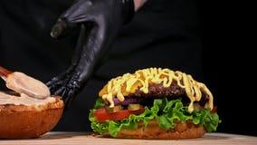 Hamburgaren lagar mat på svart bakgrund i svarta mathandskar Mycket läcker luftbulle och marmorerat nötkött Restaurang var stock video