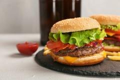 Hamburgaren med bacon kritiserar på plattan arkivfoton