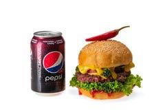 Hamburgaren med chili pepprar och kan av Pepsi arkivbild