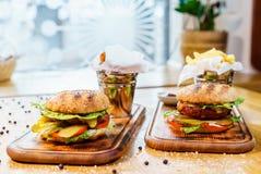 Hamburgaren med späcker, kalvköttost och grönsallat Amerikansk traditionell mat På en träbakgrund royaltyfri bild