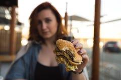 Hamburgareslut upp - den unga kvinnan som ?ter i snabbmatrestaurang - ostburgaren, medelsm?fiskar och sodavatten royaltyfria bilder
