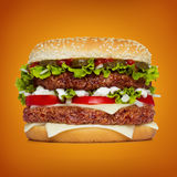 Hamburger énorme au-dessus de fond orange Image stock