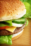 Hamburger. Delicious classic hamburger with cheese and salad in a sesame seed bun Stock Photography