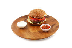 Hamburger. With sauce on a wooden dish isolated on a white background Royalty Free Stock Images