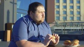 Hamburger acéré d'aliments de préparation rapide de gros homme, dîner au café extérieur, problème de manger avec excès banque de vidéos