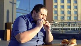 Hamburger acéré d'aliments de préparation rapide de gros homme, dîner au café extérieur, problème de manger avec excès photos libres de droits