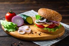 Hamburger appétissant avec du jambon, la tomate, les concombres, le fromage et la laitue, fin  image libre de droits